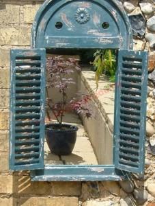 Chiếc gương được trang trí bằng những khung cửa vintage khiến khu vườn nhỏ rộng và lạ mắt.