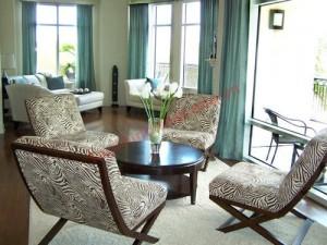Rèm xanh và tường màu kem đối lập với sàn nhà màu nâu sậm, tạo nên căn phòng phong cách đương đại rất dễ chịu